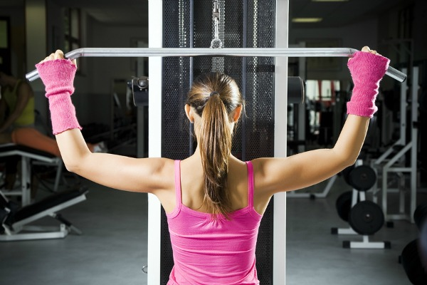 girl in a gym doing weight lifting