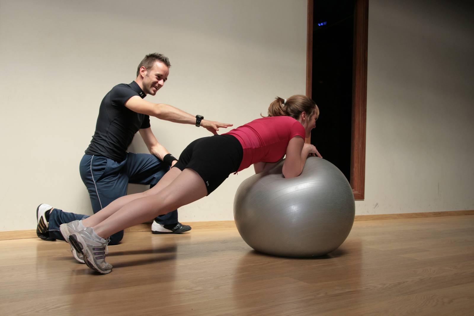 Risking Injury personal trainer balancing with swiss ball