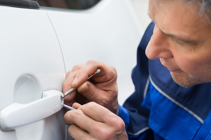 locksmith picking lock to get into vehicle