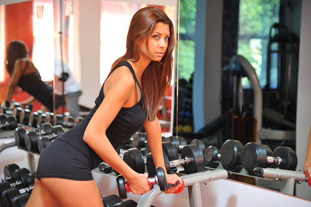 Home Gym woman with dumbbell weights on rack