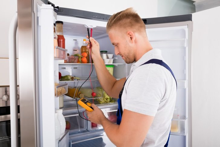 Commercial Refrigerator man checking fridge issues