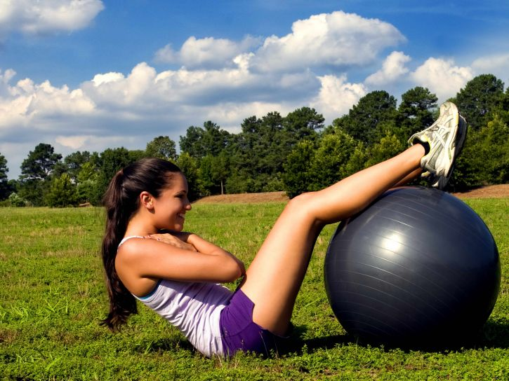 woman ab crunches on swiss ball
