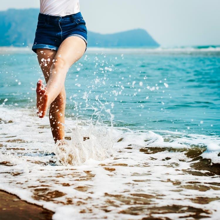 Summer woman skipping and kicking water