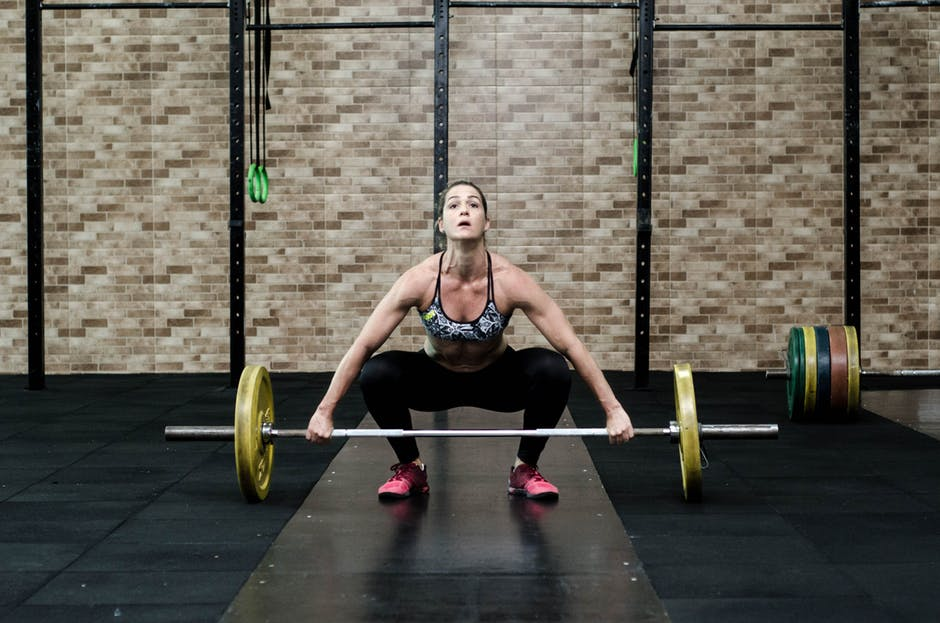 woman lifting barbell for deadlift