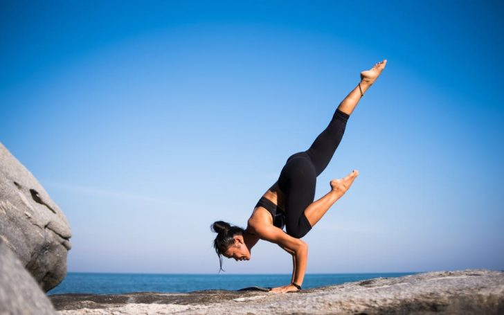exercise woman stretching on rock outside