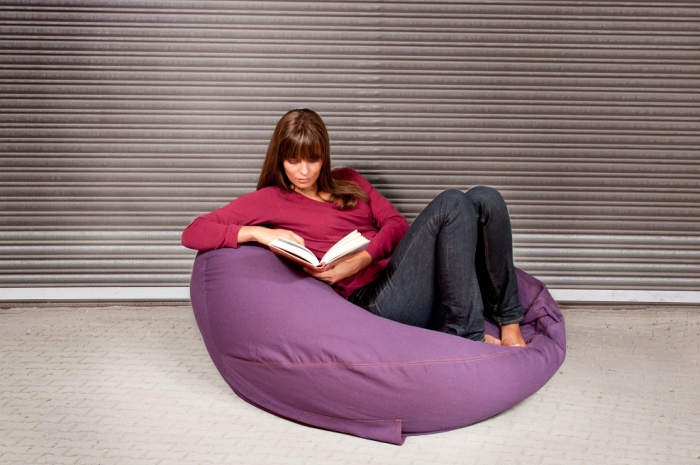 woman sitting in bean bag reading
