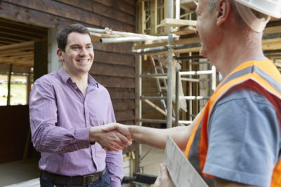 Concreter shaking hands with man