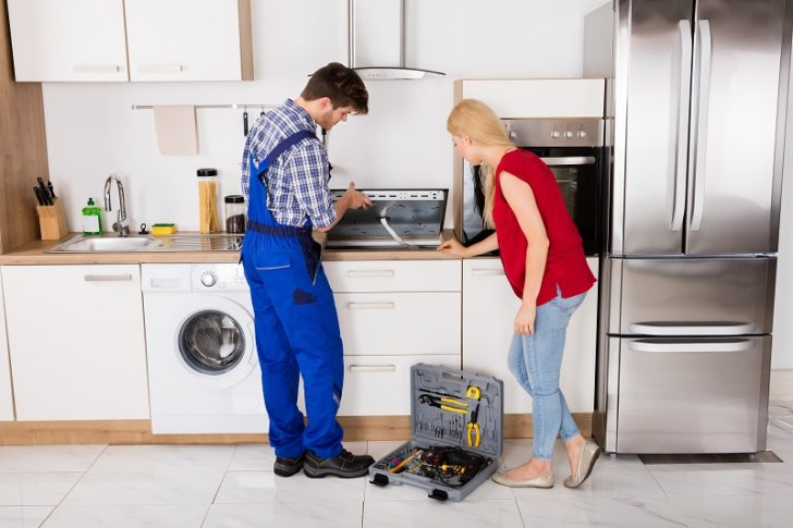 Electrician and woman inspecting appliance