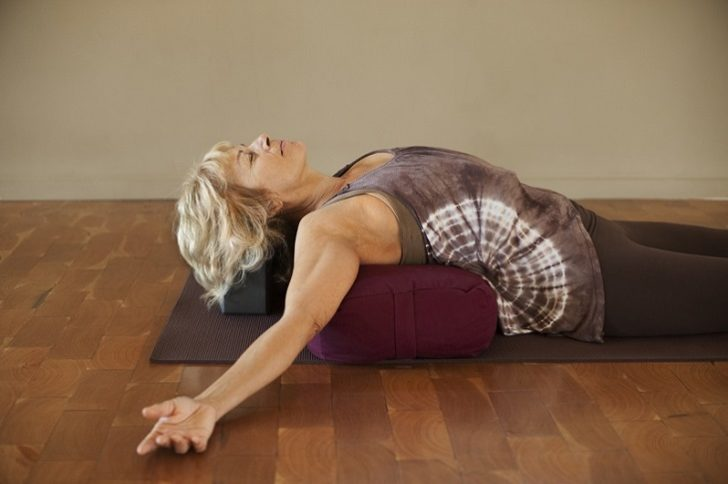 Middle age woman resting on a yoga bolster