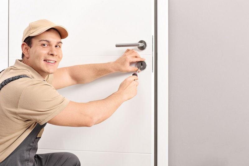Locksmith fixing lock on door