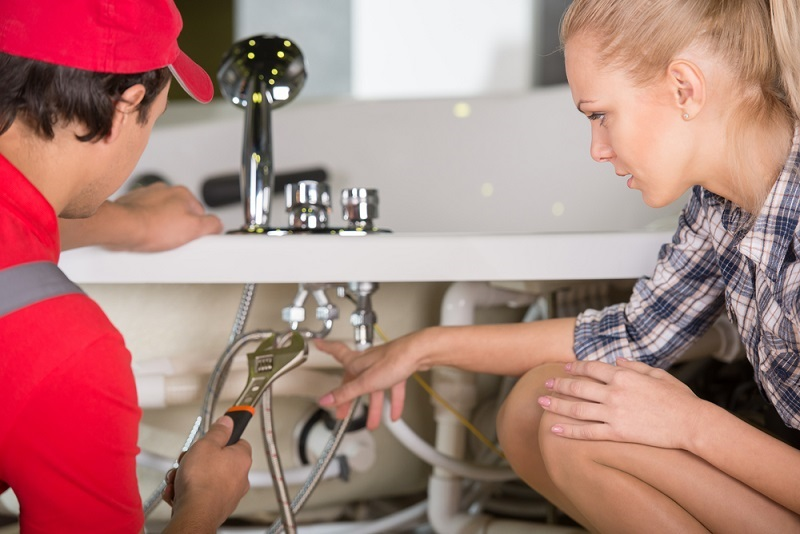 Professional Plumber talking with female homeowner