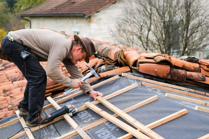 Roofing man pounding nail