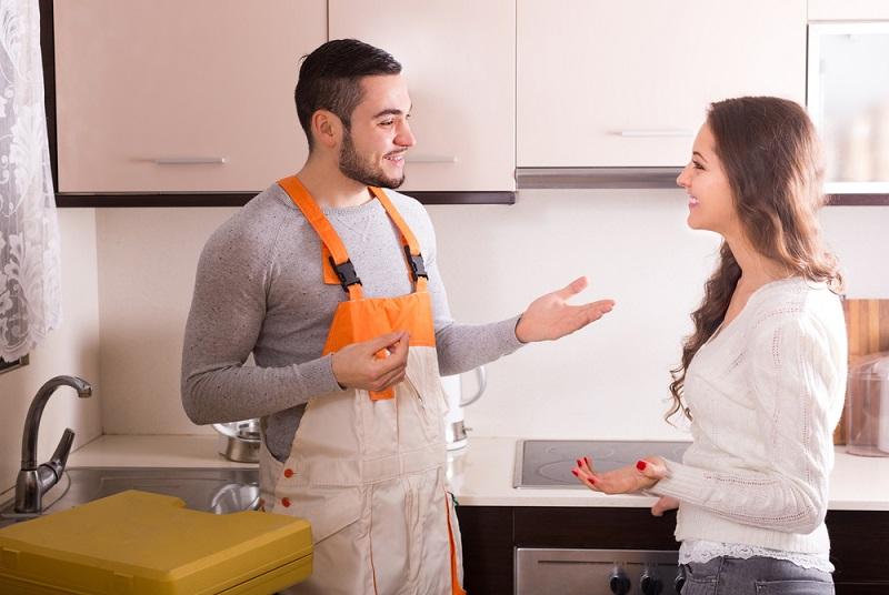 Blocked Drains plumber explaining to woman