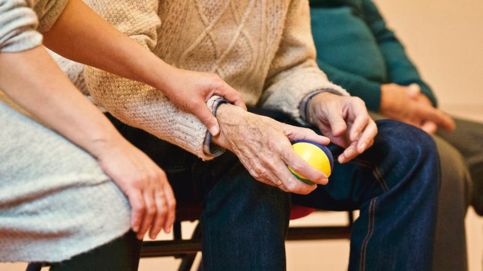 Early Aging holding stress ball with hands