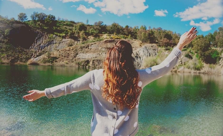 Camping woman arms in air lake