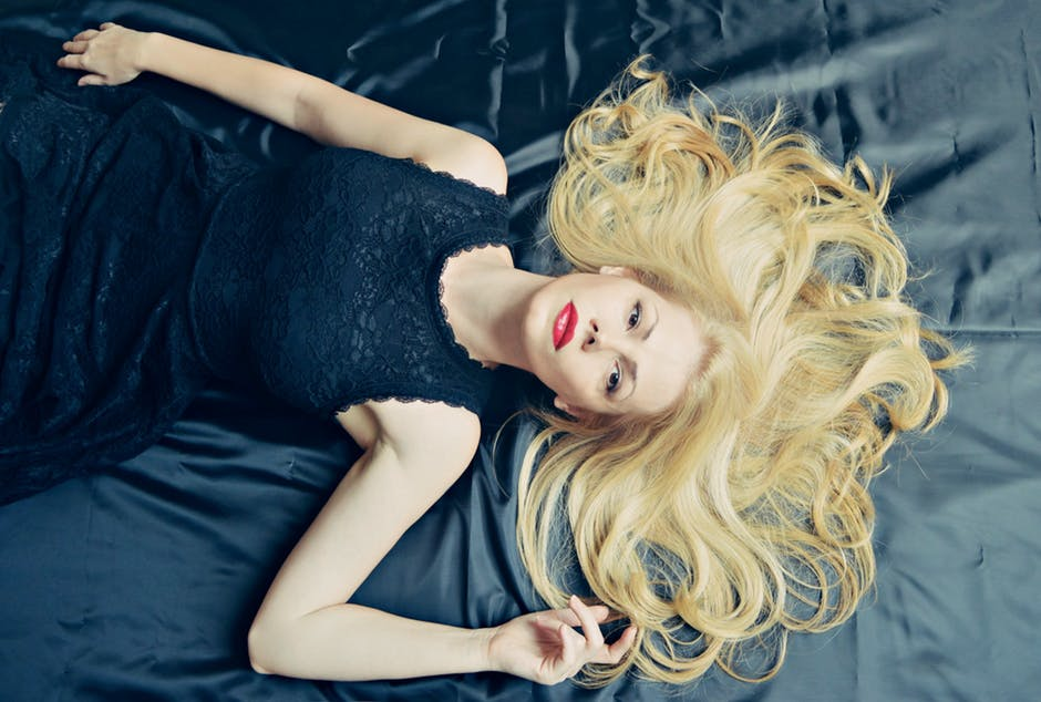 Improve Your Body laying on bed with hair strewn all over