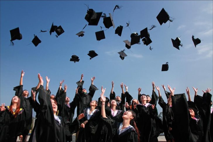 graduate throwing hats in air