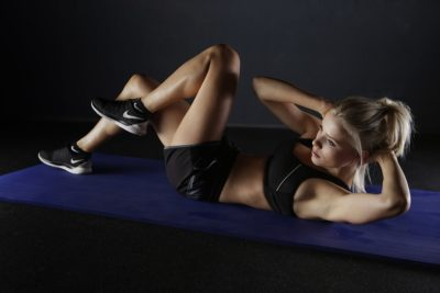 fit woman doing crunches in the dark