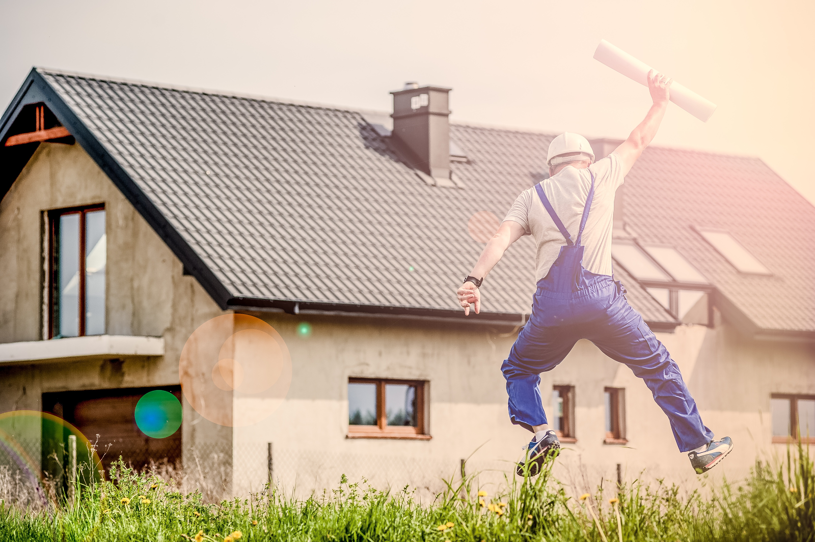 dream home plans in hand and jumping for joy