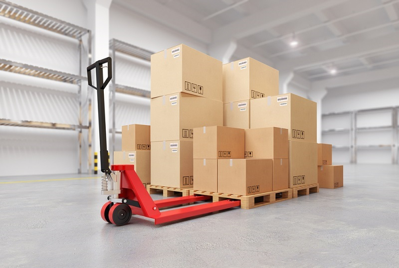 Forklifts carrying boxes through warehouse