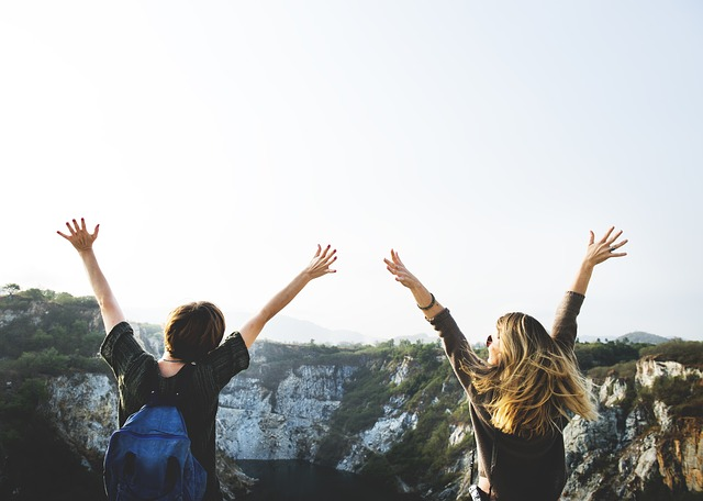 Why You Should Never Stick To A Travel Itinerary hands in the air