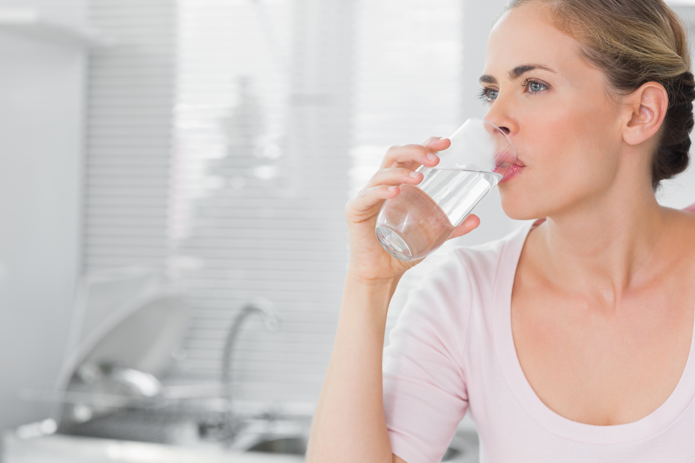 Pensive blond woman drinking water in her kitchen
