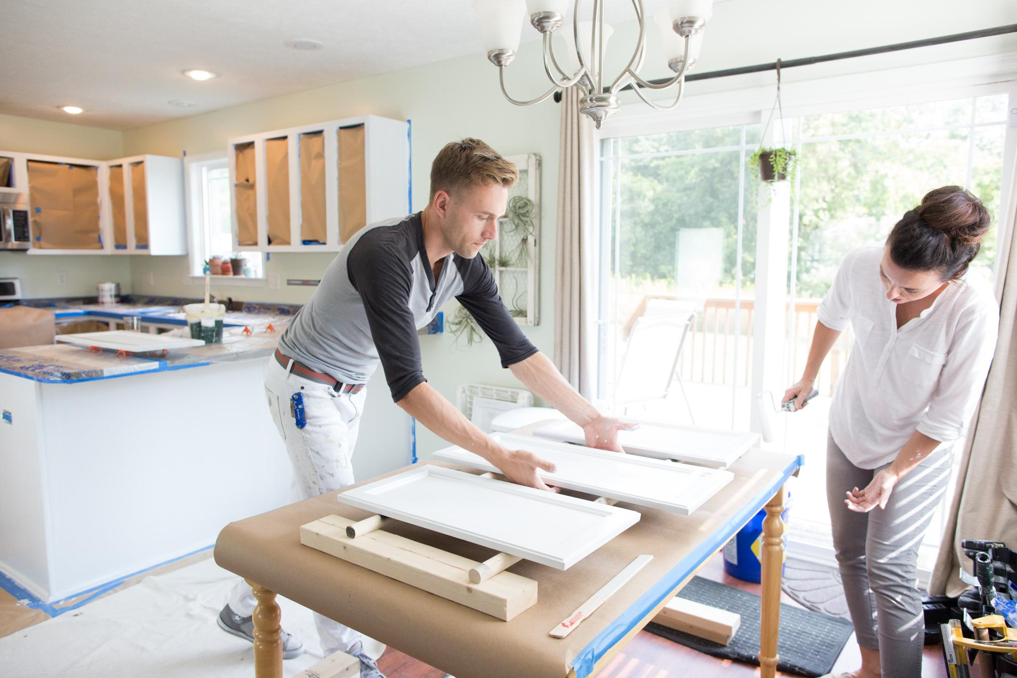 Couple Painting Kitchen Cabinets
