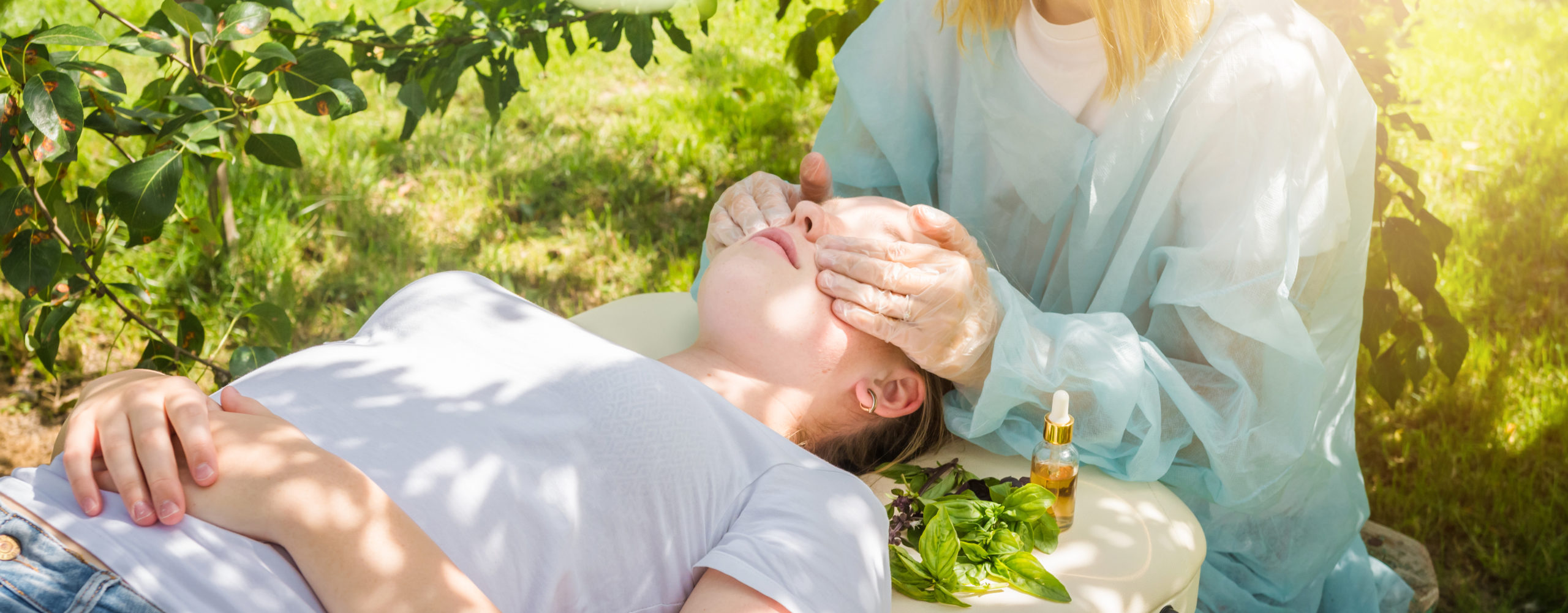 Cometologist massage therapist takes care of the skin of a girl in nature with natural cosmetics, oils for skin care, massage from natural ingredients, herbs, natural cosmetics