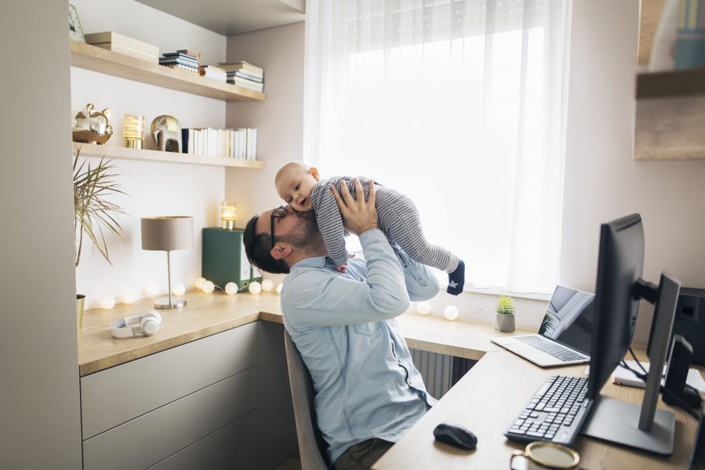 Young father working from home and babysitting his baby boy.