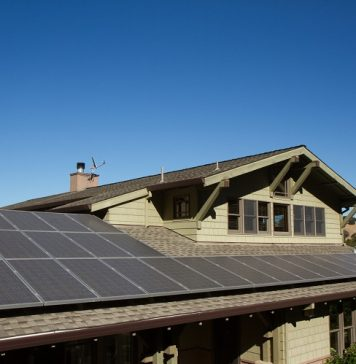 solar panels on roof of house. horizontal orientation, blue sky, gray panels on brown roof.