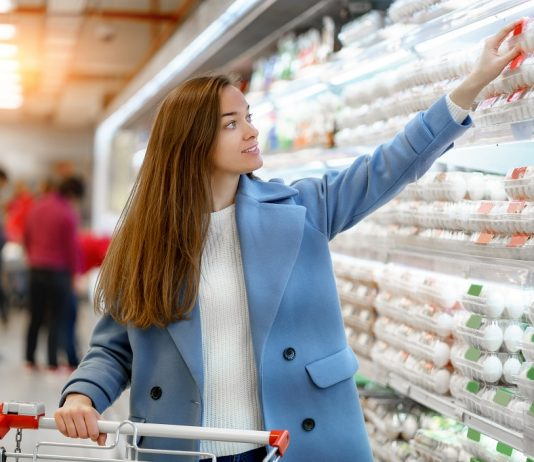 Young woman buying supermarket eggs