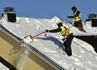 Workers with snow shovels carry out winter cleaning of roof of building from snow and ice